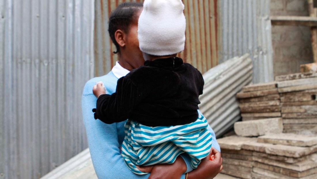 Lilian sostiene a su hija Favor en el Centro Faraja. Lilian está aprendiendo la sastrería y el trenzado del cabello con la esperanza de conseguir un trabajo cuando abandone el refugio.