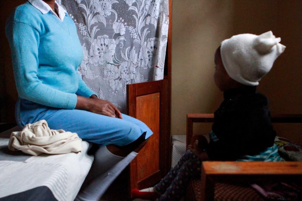 Lilian se sienta en el borde de su cama después de preparar a su hija Favor para el día.