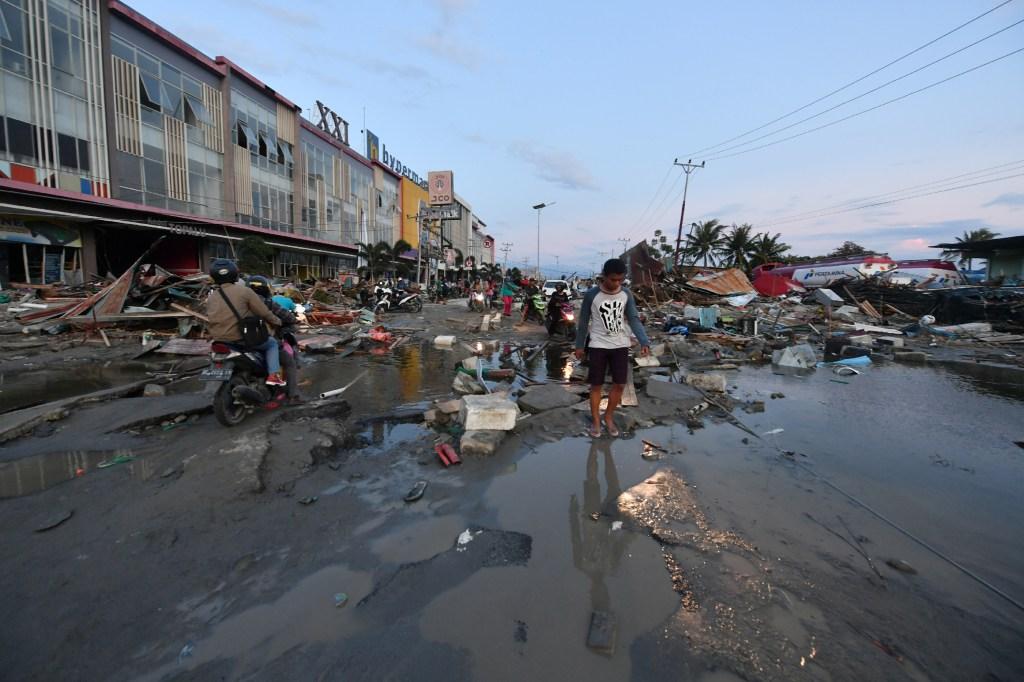 Un hombre camina sobre el suelo devastado tras tsunami en Indonecia. (Crédito: ADEK BERRY/AFP/Getty Images)