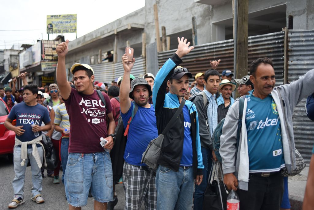 Honduran migrants heading to the United States hold up their hands as they arrive at the Casa del Migrante (Migrant's House) in Guatemala City on October 17, 2018. - A migrant caravan set out on October 13 from the impoverished, violence-plagued country and was headed north on the long journey through Guatemala and Mexico to the US border. President Donald Trump warned Honduras he will cut millions of dollars in aid if the group of about 2,000 migrants is allowed to reach the United States. (Photo by JOHAN ORDONEZ / AFP) (Photo credit should read JOHAN ORDONEZ/AFP/Getty Images)
