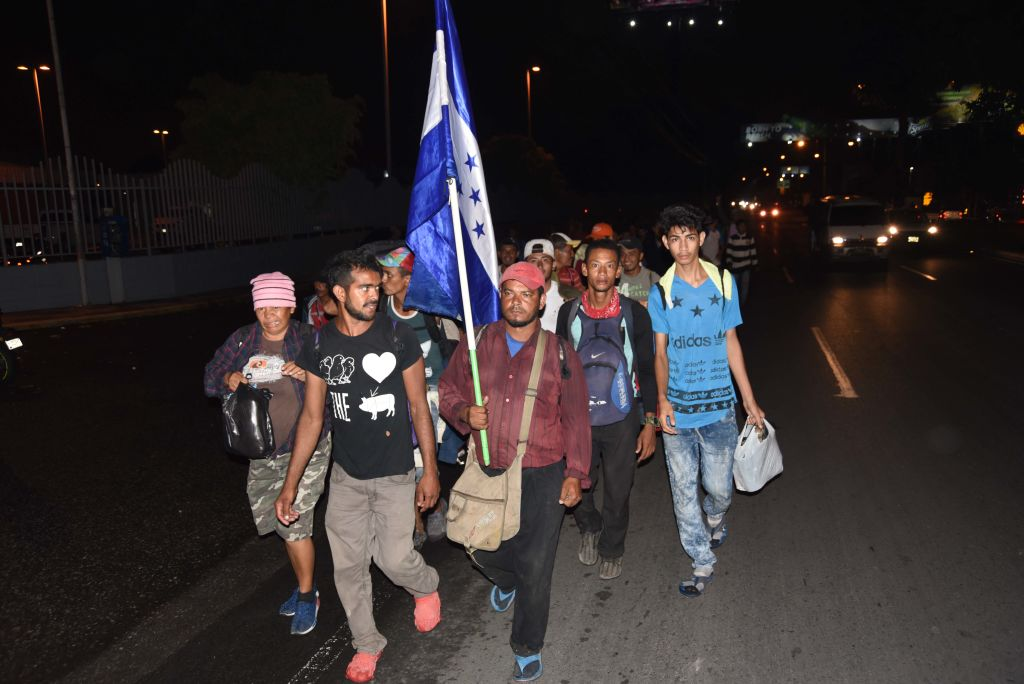 TOPSHOT - Honduran migrants taking part in a caravan to the United States arrive in Guatemala City, Guatemala, on October 17, 2018. - Thousands of Honduran migrants marched north on October 17 in a bold attempt to reach the United States, defying threats from US President Donald Trump to stop aid to countries that let them pass. (Photo by Orlando ESTRADA / AFP) (Photo credit should read ORLANDO ESTRADA/AFP/Getty Images)