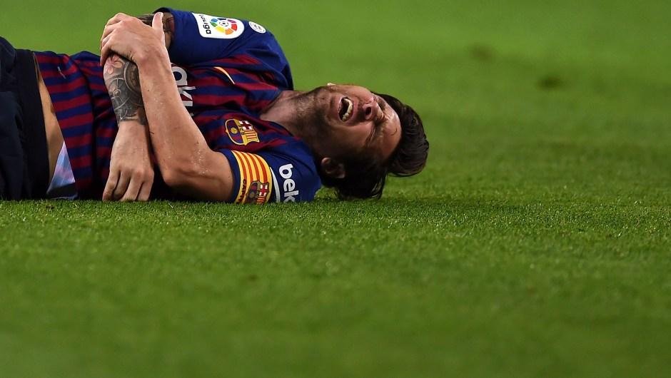 Messi hace gestos de dolor tras lesionarse el radio del brazo en el partido contra el Sevilla. (Crédito: Alex Caparros/Getty Images)