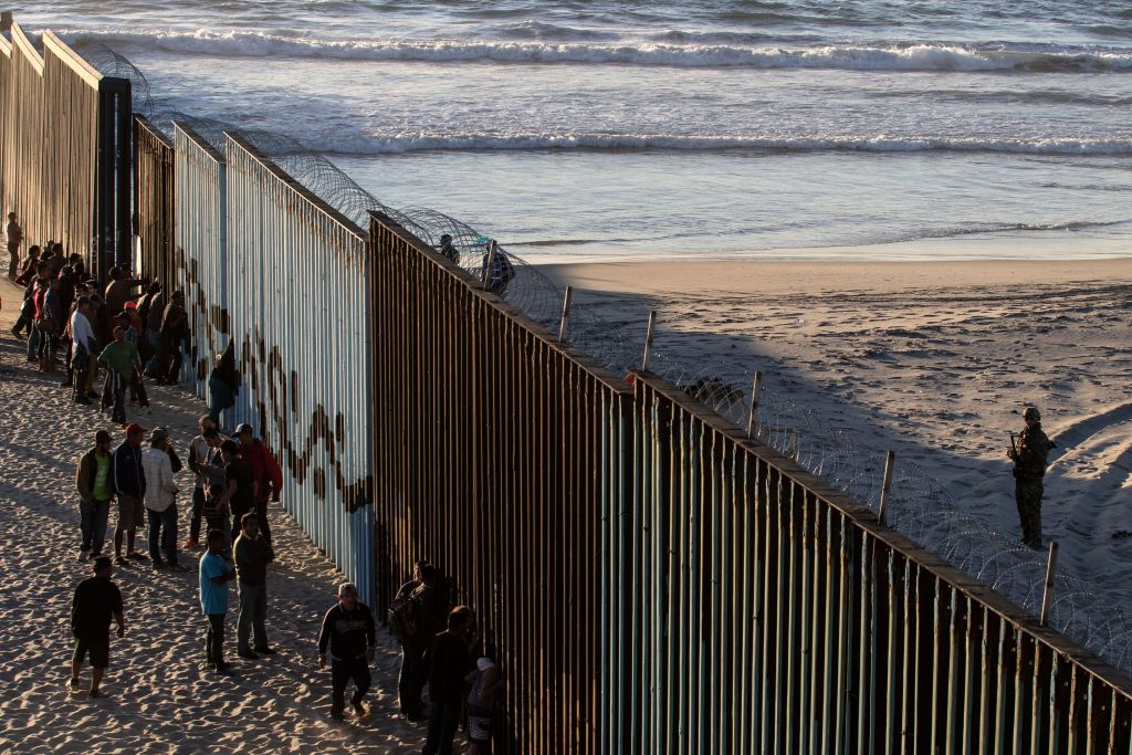 "TOPSHOT - Central American migrants moving towards the United States in hopes of a better life, stand by the US-Mexico border fence in Playas de Tijuana, Mexico, on November 14, 2018. - US Defence Secretary Jim Mattis said Tuesday he will visit the US-Mexico border, where thousands of active-duty soldiers have been deployed to help border police prepare for the arrival of a ""caravan"" of migrants. (Photo by Guillermo Arias / AFP) (Photo credit should read GUILLERMO ARIAS/AFP/Getty Images)"