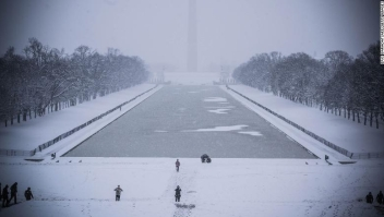 Rare tourists walk by the Lincoln Memorial Reflecting pool as snow is accumulating in Washington DC on January 13, 2019. - Washington area residents are waking up to a winter wonderland, and may need to shovel aside several inches of snow that fell overnight as a winter storm warning remains in effect until 6 p.m. Sunday and more snow is expected to fall. (Photo by Eric BARADAT / AFP) (Photo credit should read ERIC BARADAT/AFP/Getty Images)