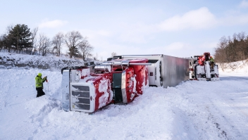 Tow truck personnel work to remove an overturned semi in the median of Interstate 90 at mile marker 218 near the U.S. Highway 52 exit Monday, Jan. 28, 2019, southeast of Rochester, Minn. According to Sgt. Troy Christianson, with the Minnesota State Patrol, the semi was eastbound and went straight off the gradual curve into the median because of blowing snow. Sgt. Christianson said there were no injuries in the crash. (Joe Ahlquist/The Rochester Post-Bulletin via AP)