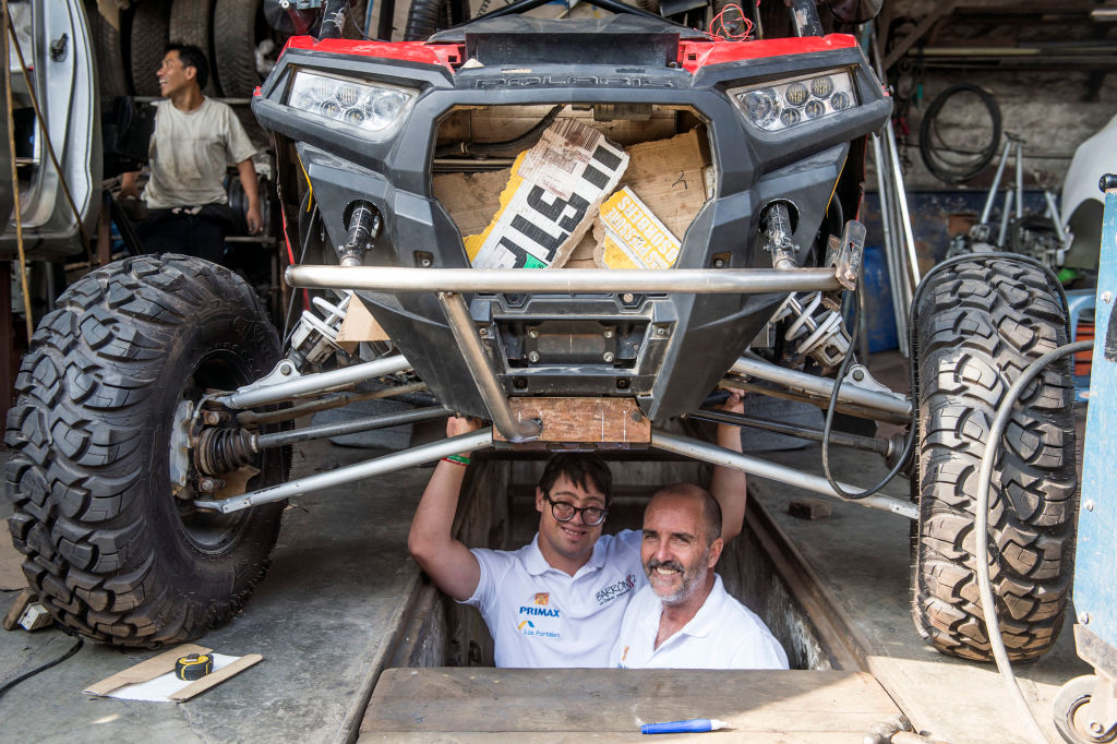 Jacques Barron (R) and his son and co-driver Lucas Barron, 25, pose under their UTV (Utility Task Vehicle) at a mechanics workshop in Lima, on December 18, 2018, where it is being prepared to take part in the upcoming Rally Dakar on January 2019. - Lucas Barron will make history on January 6 when he lines up on the Dakar 2019 start line in Peru, the first person with Down Syndrome to take part in the gruelling race. The 25-year-old, who will be co-pilot for his father Jacques, will tackle the world's most demanding rally: a 5,000 kilometer (3,000 miles), 10-day marathon, 70 percent of which will be raced over sand. (Photo by ERNESTO BENAVIDES / AFP) (Photo credit should read ERNESTO BENAVIDES/AFP/Getty Images)