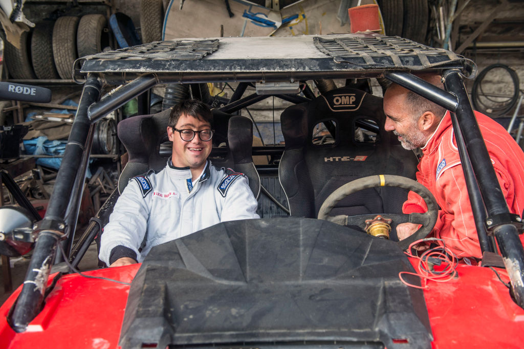 Jacques Barron (R) smiles next to his son and co-driver Lucas Barron, 25, at a mechanics workshop in Lima, on December 18, 2018, where their car is being prepared to take part in the upcoming Rally Dakar on January 2019. - Lucas Barron will make history on January 6 when he lines up on the Dakar 2019 start line in Peru, the first person with Down Syndrome to take part in the gruelling race. The 25-year-old, who will be co-pilot for his father Jacques, will tackle the world's most demanding rally: a 5,000 kilometer (3,000 miles), 10-day marathon, 70 percent of which will be raced over sand. (Photo by ERNESTO BENAVIDES / AFP) (Photo credit should read ERNESTO BENAVIDES/AFP/Getty Images)