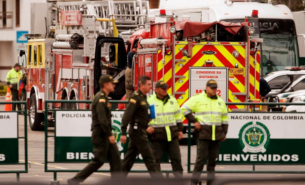 "Police officers stand guard next to a firetruck at General Santander Police Academy in Bogota, a day after a car bomb attack killed 21 people and injured more than 80, on January 18, 2019. - Defense Minister Guillermo Botero described the Thursday bombing as ""a terrorist attack committed by the ELN"" and said he had ""full evidence"" that the bomber -- earlier identified as Jose Aldemar Rojas Rodriguez, 56 -- has been a member of the ELN for more than 25 years. (Photo by DANIEL MUNOZ / AFP) (Photo credit should read DANIEL MUNOZ/AFP/Getty Images)"