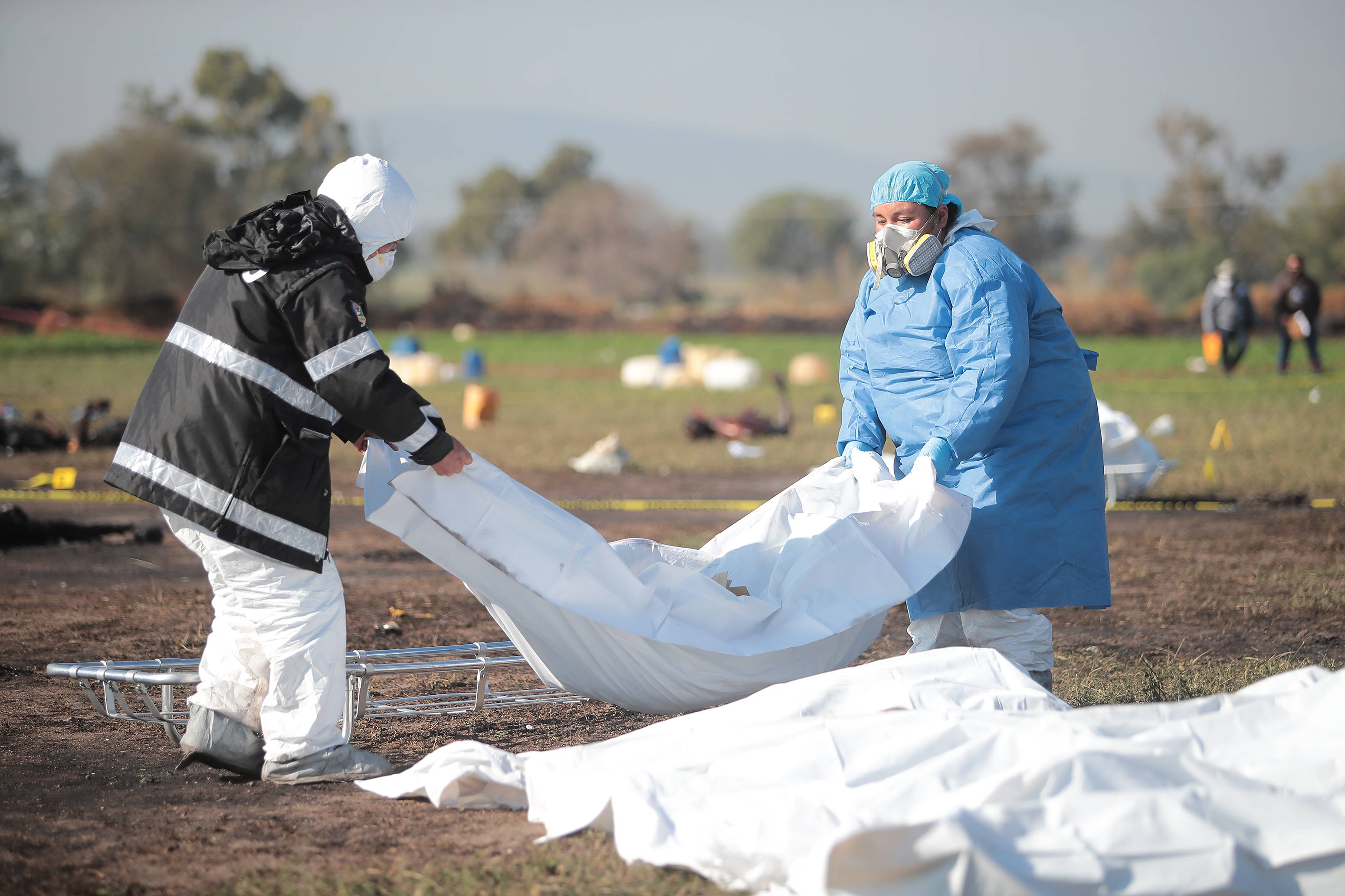 TLAHUELILPAN, MEXICO - JANUARY 19: (EDITOR'S NOTE: Image depicts graphic content) Forensic doctors work with burned bodies after an explosion in a pipeline belonging to Mexican oil company PEMEX on January 19, 2019 in Tlahuelilpan, Mexico. In a statement, PEMEX announced that the explosion was caused by the illegal manipulation of the pipeline, as minutes before the accident videos were shot where people could be seen filling drums and car fuel tanks. (Photo by Hector Vivas/Getty Images)