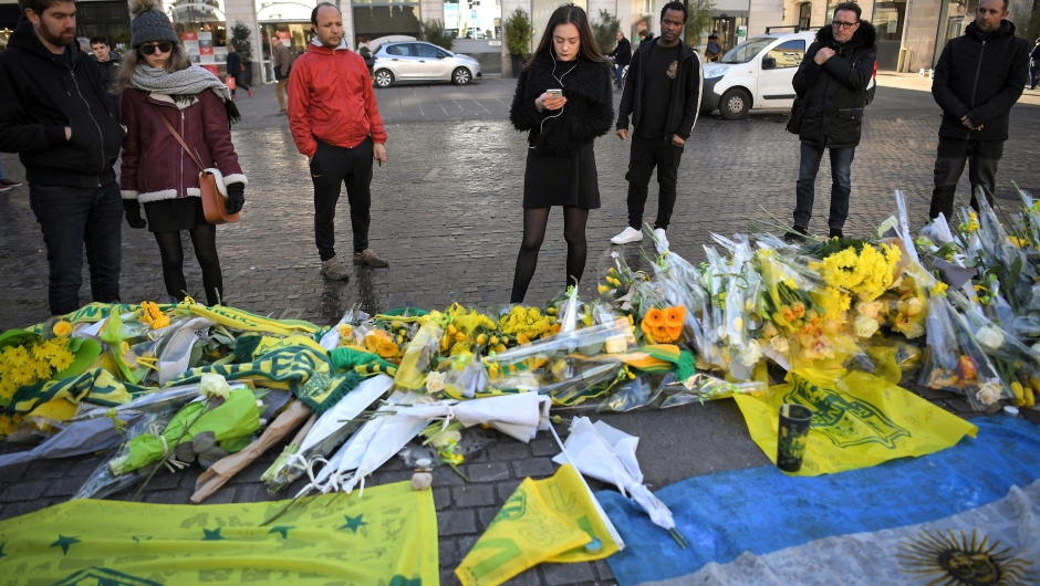 FC Nantes football club supporters looks at flowers and candles placed in the main square of the city of Nantes, western France, two days after it was announced that the plane carrying Argentinian forward Emiliano Sala vanished during a flight from Nantes to Cardiff in Wales, on January 23, 2019. - The 28-year-old Argentine striker is one of two people still missing after contact was lost with the light aircraft he was travelling on, on January 21, 2019 night. Sala was on his way to the Welsh capital to train with his new teammates for the first time after completing a £15 million pounds sterling ($19 million US dollars) move to Cardiff City from French side Nantes on January 19. (Photo by LOIC VENANCE / AFP) (Photo credit should read LOIC VENANCE/AFP/Getty Images)