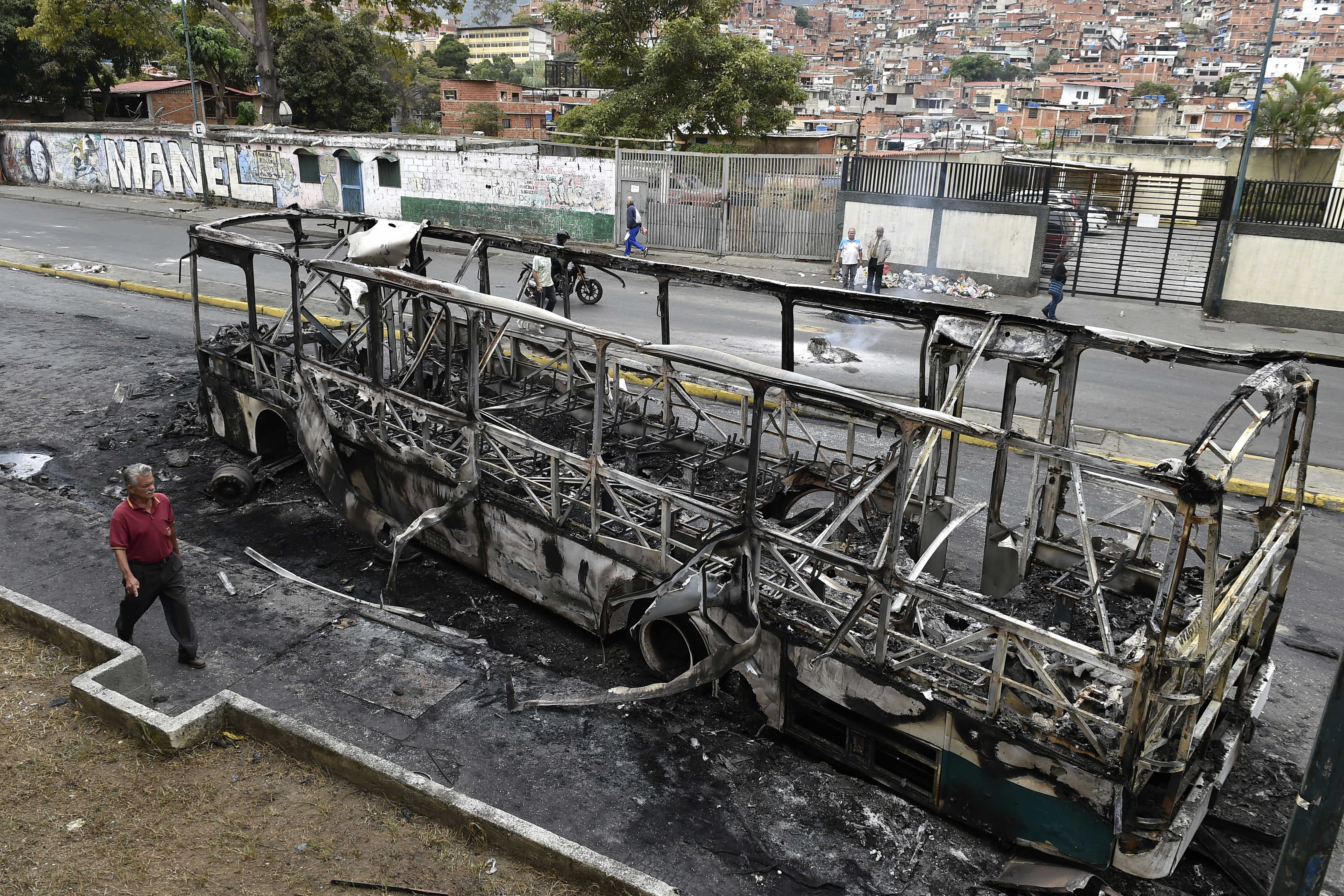 A man walks by a burned bus, that was set up on fire in Caracas on the eve of a march called by Venezuelan opposition on the anniversary of 1958 uprising that overthrew military dictatorship, on January 23, 2019. - At least four people have died following overnight clashes ahead of Wednesday's rival protests in Venezuela by supporters and opponents of President Nicolas Maduro, two days after a failed mutiny by soldiers hoping to spark a movement that would overthrow Maduro, police and non-governmental organizations said. (Photo by Luis ROBAYO / AFP) / The erroneous mention[s] appearing in the metadata of this photo by Luis ROBAYO has been modified in AFP systems in the following manner: [2019] instead of [2018. Please immediately remove the erroneous mention[s] from all your online services and delete it (them) from your servers. If you have been authorized by AFP to distribute it (them) to third parties, please ensure that the same actions are carried out by them. Failure to promptly comply with these instructions will entail liability on your part for any continued or post notification usage. Therefore we thank you very much for all your attention and prompt action. We are sorry for the inconvenience this notification may cause and remain at your disposal for any further information you may require. (Photo credit should read LUIS ROBAYO/AFP/Getty Images)
