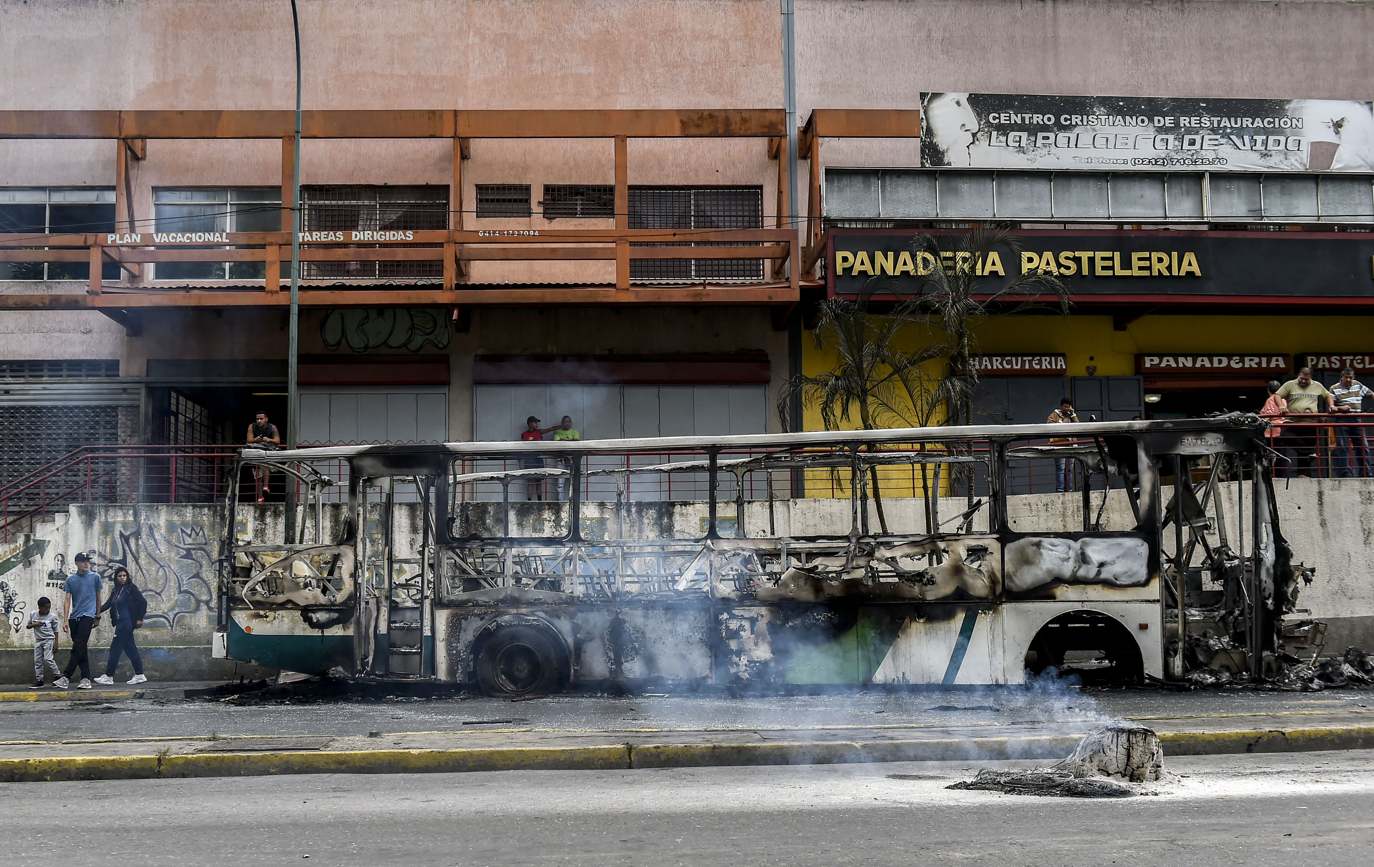 View of a burned bus, that was set up on fire in Caracas on the eve of a march called by Venezuelan opposition on the anniversary of 1958 uprising that overthrew military dictatorship, on January 23, 2019. - At least four people have died following overnight clashes ahead of Wednesday's rival protests in Venezuela by supporters and opponents of President Nicolas Maduro, two days after a failed mutiny by soldiers hoping to spark a movement that would overthrow Maduro, police and non-governmental organizations said. (Photo by Luis ROBAYO / AFP) / The erroneous mention[s] appearing in the metadata of this photo by Luis ROBAYO has been modified in AFP systems in the following manner: [2019] instead of [2018. Please immediately remove the erroneous mention[s] from all your online services and delete it (them) from your servers. If you have been authorized by AFP to distribute it (them) to third parties, please ensure that the same actions are carried out by them. Failure to promptly comply with these instructions will entail liability on your part for any continued or post notification usage. Therefore we thank you very much for all your attention and prompt action. We are sorry for the inconvenience this notification may cause and remain at your disposal for any further information you may require. (Photo credit should read LUIS ROBAYO/AFP/Getty Images)