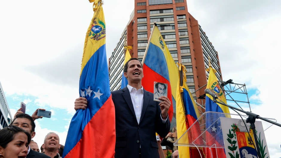 """Venezuela's National Assembly head Juan Guaido declares himself the country's """"acting president"""" during a mass opposition rally against leader Nicolas Maduro, on the anniversary of a 1958 uprising that overthrew a military dictatorship, in Caracas on January 23, 2019. - Moments earlier, the loyalist-dominated Supreme Court ordered a criminal investigation of the opposition-controlled legislature. """"I swear to formally assume the national executive powers as acting president of Venezuela to end the usurpation, (install) a transitional government and hold free elections,"""" said Guaido as thousands of supporters cheered. (Photo by Federico PARRA / AFP) (Photo credit should read FEDERICO PARRA/AFP/Getty Images)"""