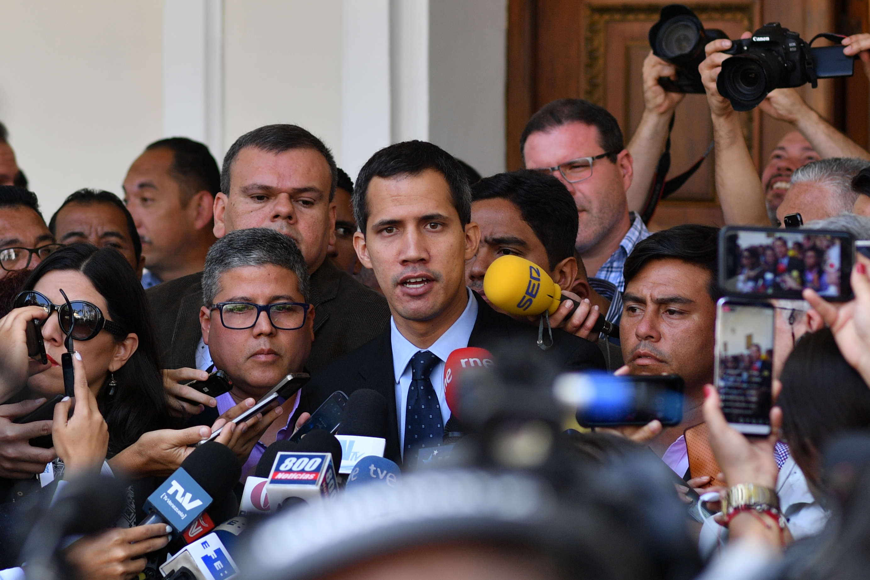 """Venezuela's National Assembly head and self-proclaimed """"acting president"""" Juan Guaido, talks to journalists upon arrival at the National Assembly in Caracas on January 29, 2019. - Venezuela's Attorney General Tarek William Saab asked the Supreme Court on Tuesday to bar self-proclaimed acting president and opposition leader Juan Guaido from leaving the country and to freeze his assets. (Photo by Yuri CORTEZ / AFP) (Photo credit should read YURI CORTEZ/AFP/Getty Images)"""