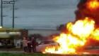 Varios hombres sacan a una mujer de un vehículo en llamas