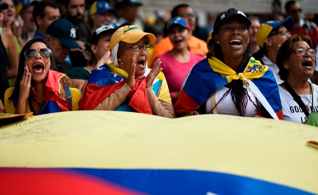 TOPSHOT - Supporters of Venezuelan opposition leader and self declared acting president Juan Guaido, cheer as they start gathering for a rally to press the military to let in US humanitarian aid, in eastern Caracas on February 12, 2019. - The tug of war between the government and opposition is centred on whether humanitarian aid will be allowed into the economically crippled country, which suffers shortages of food, medicine and other basics. (Photo by Federico PARRA / AFP) (Photo credit should read FEDERICO PARRA/AFP/Getty Images)
