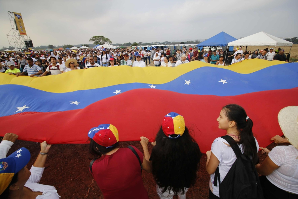 "People wait for the start of ""Venezuela Aid Live"" concert, organized by British billionaire Richard Branson to raise money for the Venezuelan relief effort at Tienditas International Bridge in Cucuta, Colombia, on February 22, 2019 - The concert was organized by British billionaire Richard Branson to raise money for the Venezuelan relief effort. Venezuela's political tug-of-war morphs into a battle of the bands on Friday, with dueling government and opposition pop concerts ahead of a weekend showdown over the entry of badly needed food and medical aid. (Photo by SCHNEYDER MENDOZA / AFP) (Photo credit should read SCHNEYDER MENDOZA/AFP/Getty Images)"