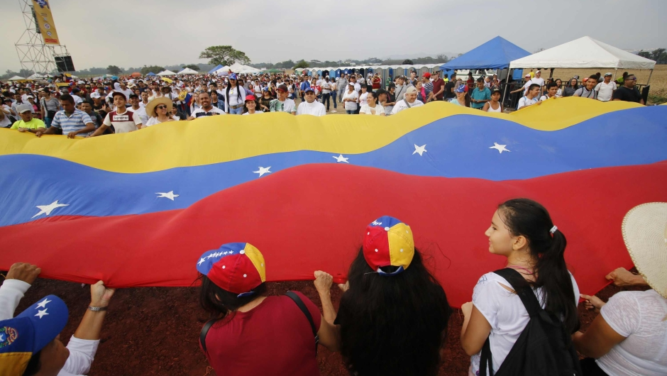 """People wait for the start of """"Venezuela Aid Live"""" concert, organized by British billionaire Richard Branson to raise money for the Venezuelan relief effort at Tienditas International Bridge in Cucuta, Colombia, on February 22, 2019 - The concert was organized by British billionaire Richard Branson to raise money for the Venezuelan relief effort. Venezuela's political tug-of-war morphs into a battle of the bands on Friday, with dueling government and opposition pop concerts ahead of a weekend showdown over the entry of badly needed food and medical aid. (Photo by SCHNEYDER MENDOZA / AFP) (Photo credit should read SCHNEYDER MENDOZA/AFP/Getty Images)"""
