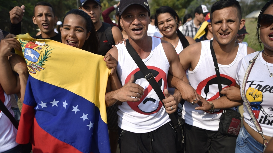 """People carry Venezuelan flags as they walk to the place where """"Venezuela Aid Live"""" concert will be held at Tienditas International Bridge in Cucuta, Colombia, on February 22, 2019. - The concert was organized by British billionaire Richard Branson to raise money for the Venezuelan relief effort. Venezuela's political tug-of-war morphs into a battle of the bands on Friday, with dueling government and opposition pop concerts ahead of a weekend showdown over the entry of badly needed food and medical aid. (Photo by Luis ROBAYO / AFP) (Photo credit should read LUIS ROBAYO/AFP/Getty Images)"""
