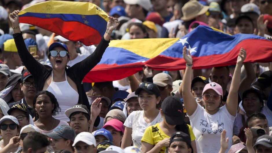 """People wait for the start of """"Venezuela Aid Live"""" concert, organized by British billionaire Richard Branson to raise money for the Venezuelan relief effort at Tienditas International Bridge in Cucuta, Colombia, on February 22, 2019. - Venezuela's political tug-of-war morphs into a battle of the bands on Friday, with dueling government and opposition pop concerts ahead of a weekend showdown over the entry of badly needed food and medical aid. (Photo by RAUL ARBOLEDA / AFP) (Photo credit should read RAUL ARBOLEDA/AFP/Getty Images)"""