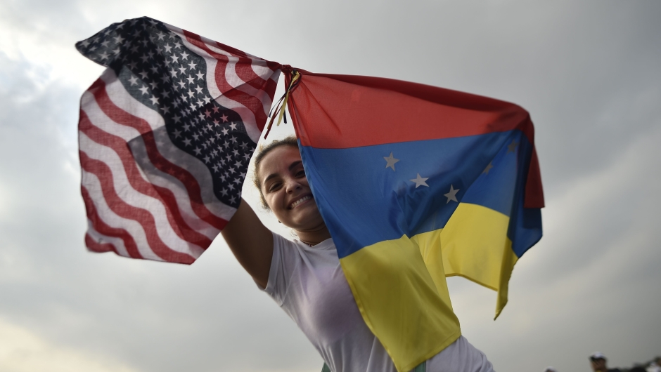 """A woman holds the Venezuelan and US flags as she waits for the start of """"Venezuela Aid Live"""" concert, organized by British billionaire Richard Branson to raise money for the Venezuelan relief effort at Tienditas International Bridge in Cucuta, Colombia, on February 22, 2019 - The concert was organized by British billionaire Richard Branson to raise money for the Venezuelan relief effort. Venezuela's political tug-of-war morphs into a battle of the bands on Friday, with dueling government and opposition pop concerts ahead of a weekend showdown over the entry of badly needed food and medical aid. (Photo by Luis ROBAYO / AFP) (Photo credit should read LUIS ROBAYO/AFP/Getty Images)"""