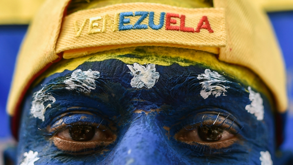 """A man with his face painted with Venezuela's national colours, attends the """"Venezuela Aid Live"""" concert, organized to raise money for the Venezuelan relief effort at Tienditas International Bridge in Cucuta, Colombia, on February 22, 2019. - Thousands of people, many waving Venezuelan flags, streamed into a concert site on the Venezuela-Colombia border Friday for an international charity concert to push for humanitarian aid deliveries in defiance of a blockade by the government of President Nicolas Maduro. (Photo by Luis ROBAYO / AFP) (Photo credit should read LUIS ROBAYO/AFP/Getty Images)"""