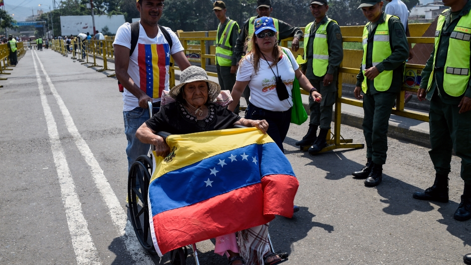 """Venezuelans cross the Simon Bolivar International Brige from San Antonio del Tachira in Venezuela, to attend the """"Venezuela Aid Live"""" concert on the Colombian side of Tienditas International Bridge in Cucuta, Colombia on February 22, 2019. - Thousands of people, many waving Venezuelan flags, streamed into a concert site on the Venezuela-Colombia border Friday for an international charity concert to push for humanitarian aid deliveries in defiance of a blockade by the government of President Nicolas Maduro. (Photo by Federico Parra / AFP) (Photo credit should read FEDERICO PARRA/AFP/Getty Images)"""