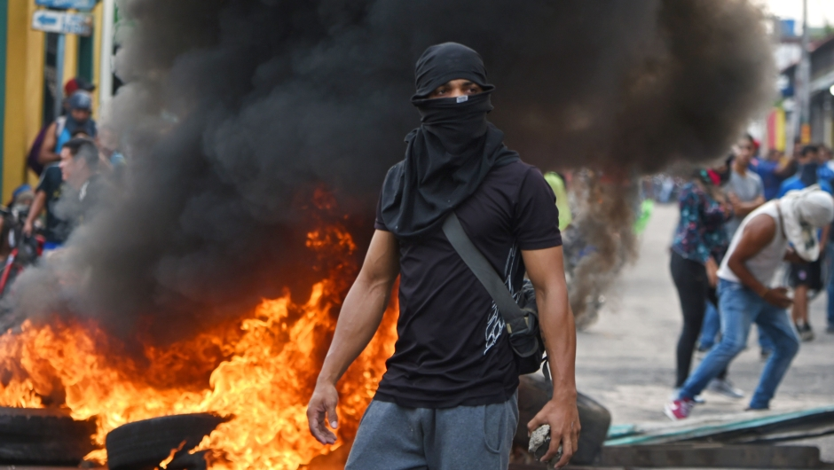 TOPSHOT - Venezuelans clash with national guards in the border town of Ureña after Maduro´s government ordered to temporary close down the border with Colombia on February 23, 2019. - Venezuela braced for a showdown between the military and regime opponents at the Colombian border on Saturday, when self-declared acting president Juan Guaido has vowed humanitarian aid would enter his country despite a blockade (Photo by JUAN BARRETO / AFP) (Photo credit should read JUAN BARRETO/AFP/Getty Images)