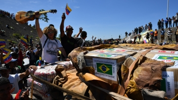People cheer as trucks with humanitarian aid to Venezuela approach the Brazil-Venezuela border in Pacaraima, Roraima state, Brazil on February 23, 2019. - Venezuela braced for a showdown between the military and regime opponents at the Colombian border on Saturday, when self-declared acting president Juan Guaido has vowed humanitarian aid would enter his country despite a blockade. Early Saturday two large trucks -driven by Venezuelans and escorted by Brazilian police- carrying eight tonnes of emergency aid left Boa Vista in Brazil en route to the Venezuelan border. (Photo by Nelson Almeida / AFP) (Photo credit should read NELSON ALMEIDA/AFP/Getty Images)