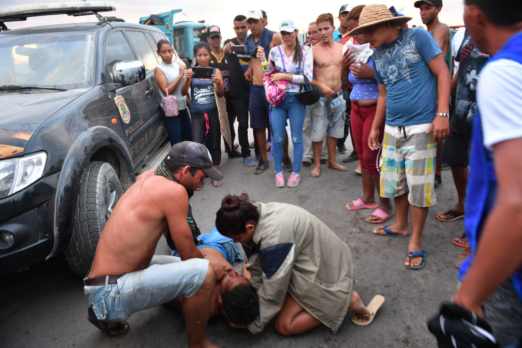 Opposition demonstrators assist an injured protester on the Brazilian side of the border between Venezuela and Pacaraima, Roraima state, Brazil, where clashes erupted amid efforts to take aid into the crisis-hit country, on February 23, 2019. - A high-risk opposition campaign to deliver humanitarian aid into Venezuela descended into chaos Saturday after President Nicolas Maduro's security forces fired on demonstrators and aid trucks were set ablaze as his blockade held firm. Two people, including a 14-year-old boy, were killed in clashes with security forces on the Brazil-Venezuela border amid efforts to bring in aid there, a human rights group said. (Photo by Nelson Almeida / AFP) (Photo credit should read NELSON ALMEIDA/AFP/Getty Images)