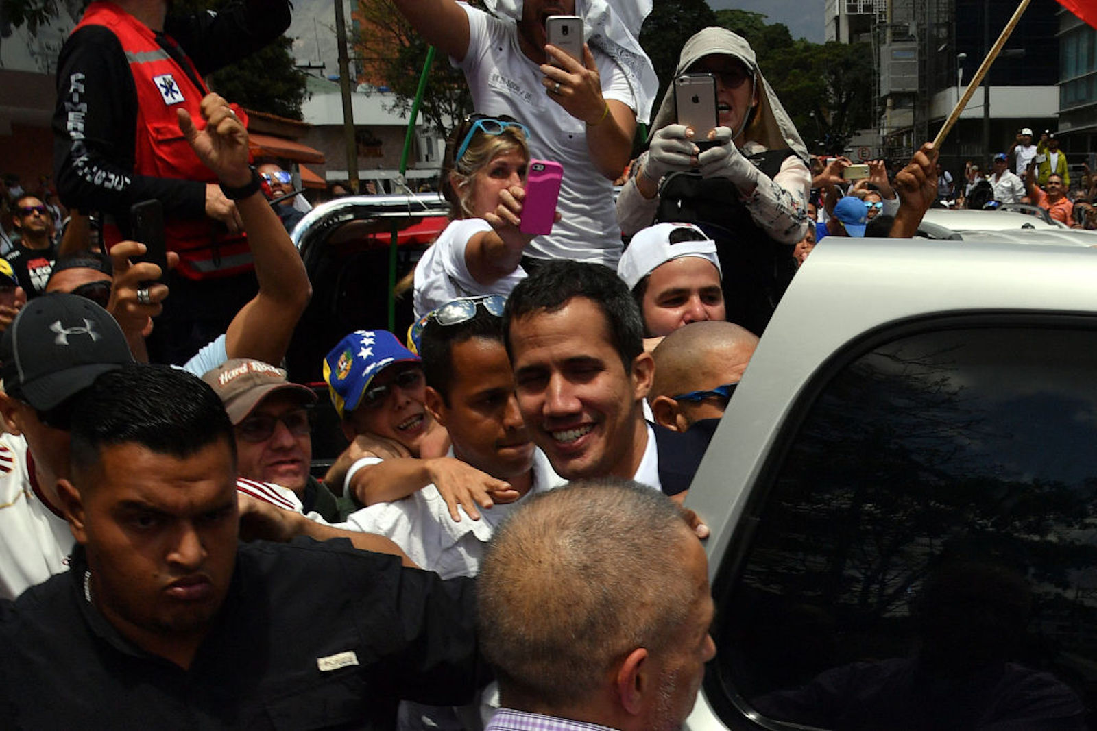 Venezuelan opposition leader and self-proclaimed acting president Juan Guaido (C) is surrounded by supporters upon his arrival in Caracas on March 4, 2019. - Venezuela's opposition leader Juan Guaido was mobbed by supporters, media and the ambassadors of allied countries as he returned to Caracas on Monday, defying the threat of arrest from embattled President Nicolas Maduro's regime. Just before his arrival, US Vice President Mike Pence sent a warning to Maduro to ensure Guaido's safety. (Photo by Yuri CORTEZ / AFP) (Photo credit should read YURI CORTEZ/AFP/Getty Images)