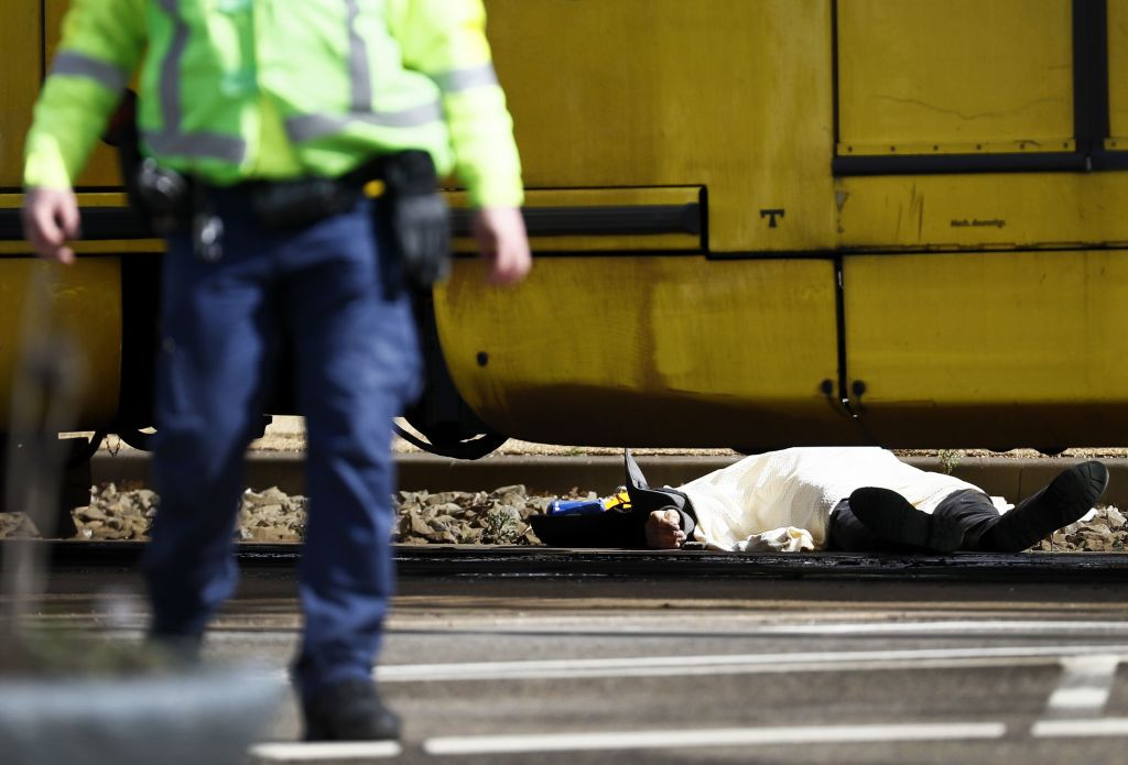 EDITORS NOTE: Graphic content / A body lying on the ground is covered near a tram at the 24 Oktoberplace in Utrecht, on March 18, 2019 where a shooting took place. - A gunman who opened fire on a tram in the Dutch city of Utrecht on March 18, injuring several people, is on the run, police said. Police only spoke of one gunman but did not rule out the possibility there might be others, the ANP news agency quoted police as saying. (Photo by Robin van Lonkhuijsen / ANP / AFP) / Netherlands OUT (Photo credit should read ROBIN VAN LONKHUIJSEN/AFP/Getty Images)