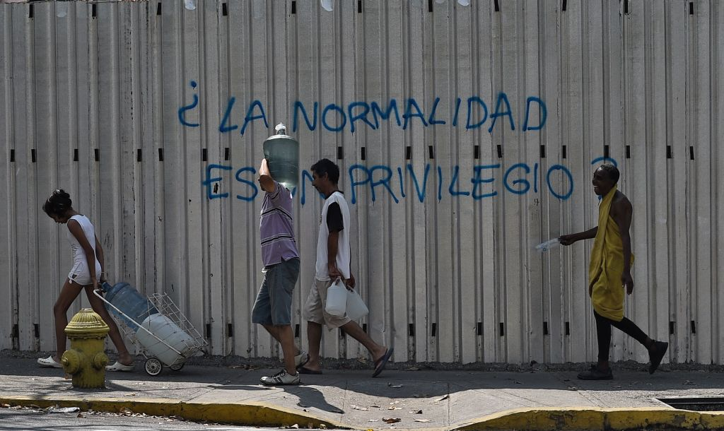 """People walk past a graffiti reading """"Is Normality a Privilege?"""" during a new power outage in Venezuela, at Fuerzas Armadas Avenue in Caracas on March 31, 2019. - Living conditions are plummeting in the oil-producing Latin American nation, which is spiralling ever deeper into economic chaos during a protracted political crisis. (Photo by Federico PARRA / AFP) (Photo credit should read FEDERICO PARRA/AFP/Getty Images)"""