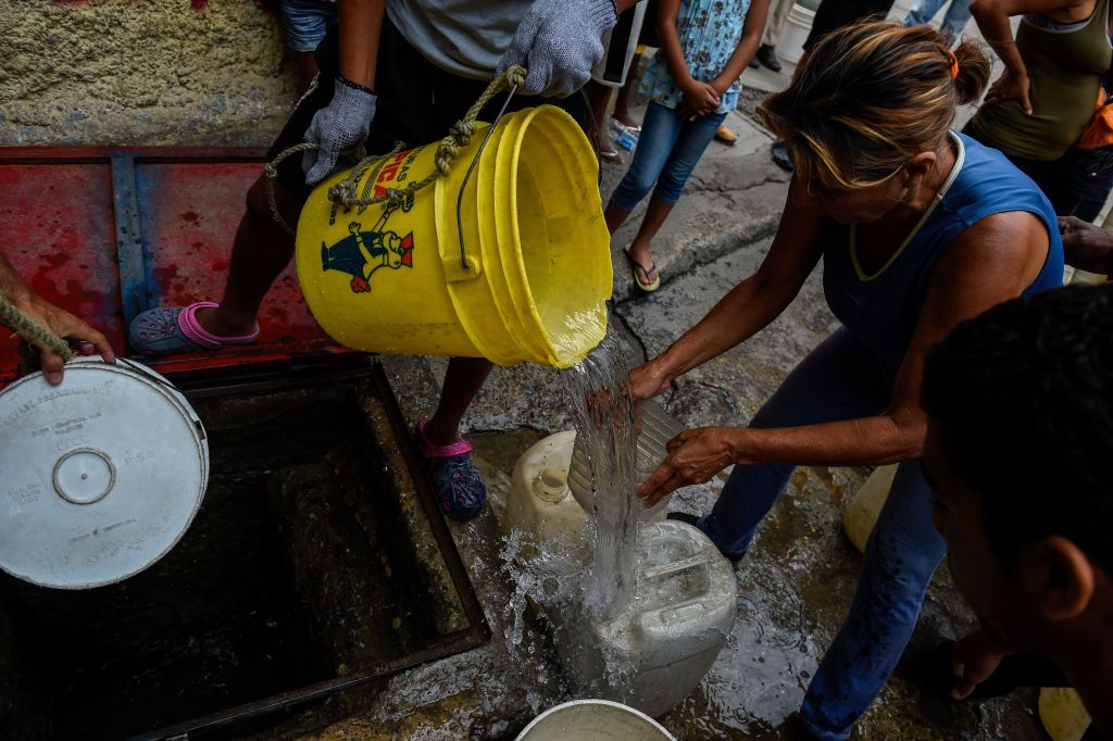 People draw water from a spring water tank to be used in their toilets, at Petare neighborhood in Caracas on April 1, 2019. - Venezuela's President Nicolas Maduro announced 30 days of electricity rationing Sunday, after his government said it was shortening the working day and keeping schools closed due to blackouts. (Photo by Federico Parra / AFP) (Photo credit should read FEDERICO PARRA/AFP/Getty Images)