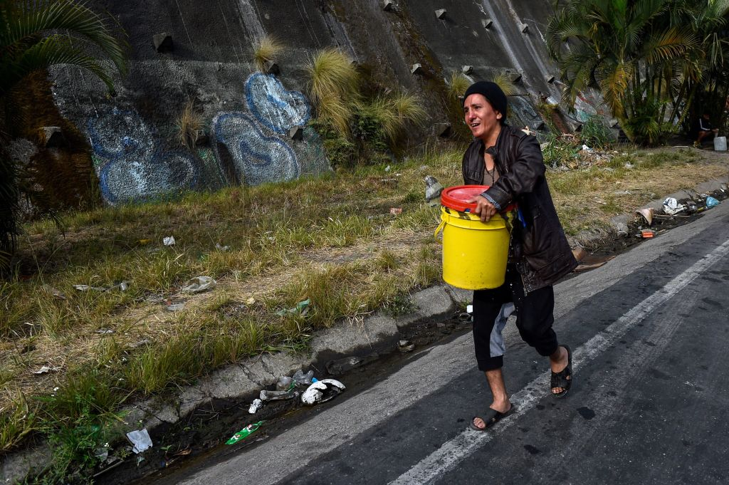 A man carries a can with water he collected from a spring water tank to be used in his toilet, at Petare neighborhood in Caracas on April 1, 2019. - Venezuela's President Nicolas Maduro announced 30 days of electricity rationing Sunday, after his government said it was shortening the working day and keeping schools closed due to blackouts. (Photo by FEDERICO PARRA / AFP) (Photo credit should read FEDERICO PARRA/AFP/Getty Images)