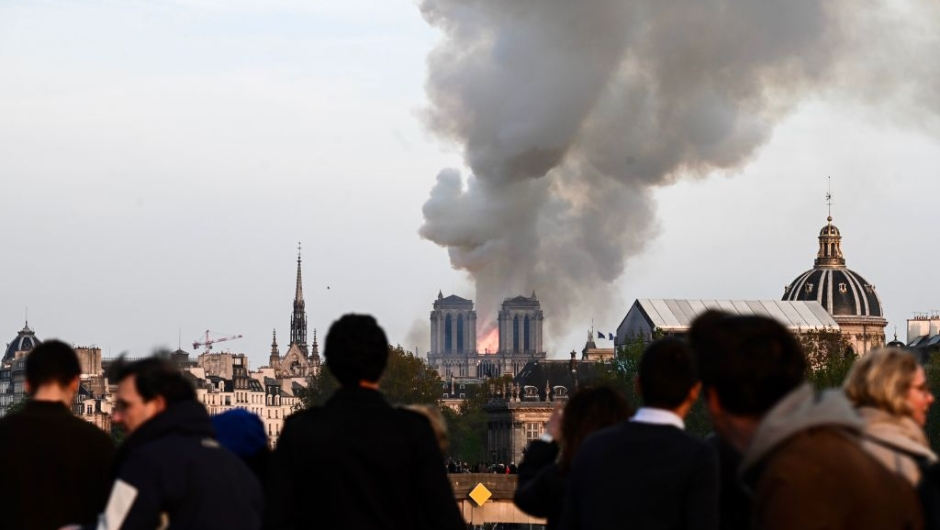 People watch the landmark Notre-Dame Cathedral burning in central Paris on April 15, 2019. - A huge fire swept through the roof of the famed Notre-Dame Cathedral in central Paris on April 15, 2019, sending flames and huge clouds of grey smoke billowing into the sky. The flames and smoke plumed from the spire and roof of the gothic cathedral, visited by millions of people a year. A spokesman for the cathedral told AFP that the wooden structure supporting the roof was being gutted by the blaze. (Photo by Philippe LOPEZ / AFP) (Photo credit should read PHILIPPE LOPEZ/AFP/Getty Images)