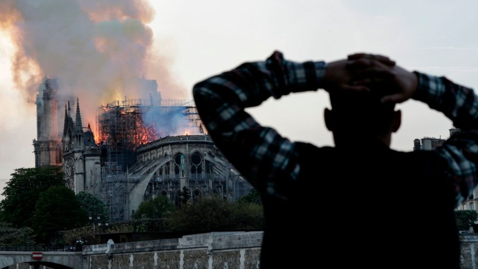 A man watches the landmark Notre-Dame Cathedral burn, engulfed in flames, in central Paris on April 15, 2019. - A huge fire swept through the roof of the famed Notre-Dame Cathedral in central Paris on April 15, 2019, sending flames and huge clouds of grey smoke billowing into the sky. The flames and smoke plumed from the spire and roof of the gothic cathedral, visited by millions of people a year. A spokesman for the cathedral told AFP that the wooden structure supporting the roof was being gutted by the blaze. (Photo by Geoffroy VAN DER HASSELT / AFP) (Photo credit should read GEOFFROY VAN DER HASSELT/AFP/Getty Images)