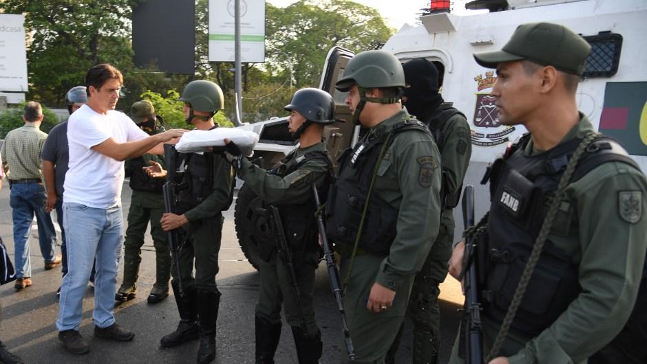 Un venezolano entrega comida a miembros de las fuerzas de seguridad en Caracas el 30 de abril de 2019. Crédito: YURI CORTEZ / AFP / Getty Images.