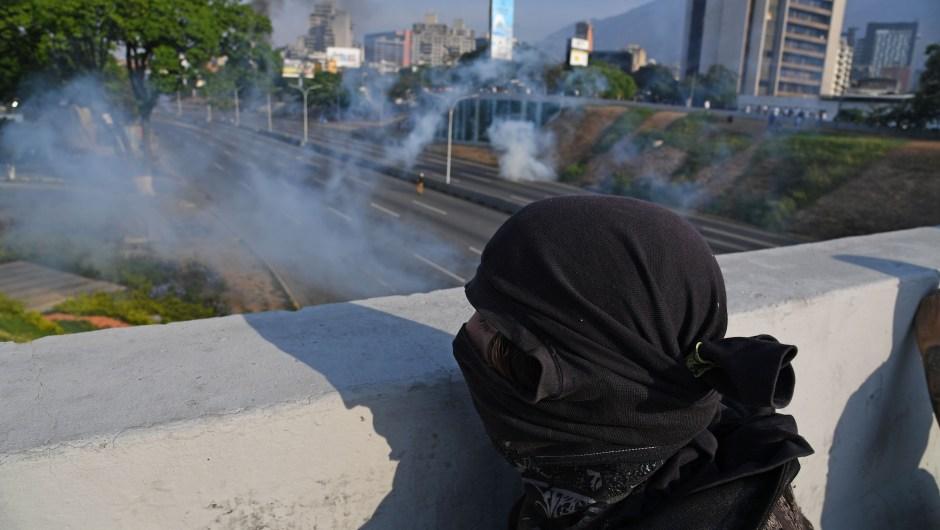 Un hombre se cubre durante los enfrentamientos con las fuerzas de seguridad en Caracas el 30 de abril de 2019. Crédito: YURI CORTEZ / AFP / Getty Images