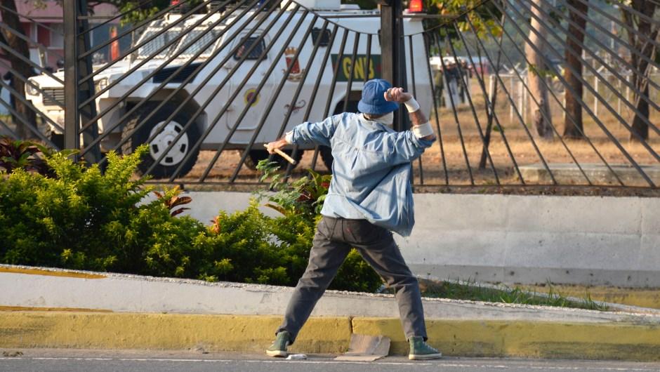 Un manifestante lanza una piedra a un vehículo de la Guardia Nacional el 30 de abril de 2019 en Caracas, Venezuela. Crédito: Rafael Briceño / Getty Images