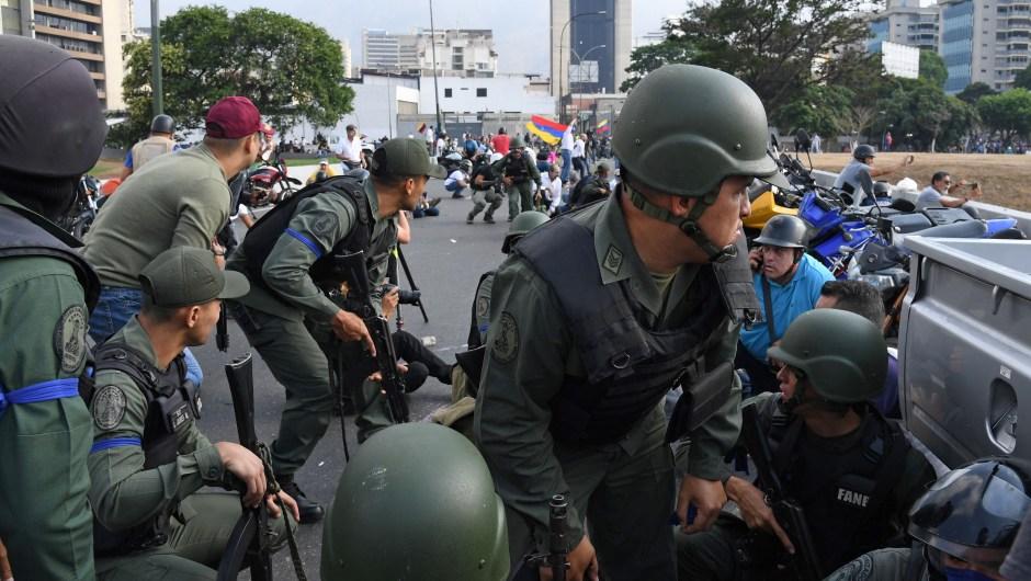 Los miembros de la Guardia Nacional Bolivariana que apoyan al líder opositor venezolano y autoproclamado presidente Juan Guaidó toman posiciones frente a la base de La Carlota en Caracas el 30 de abril de 2019. Crédito: YURI CORTEZ / AFP / Getty Images