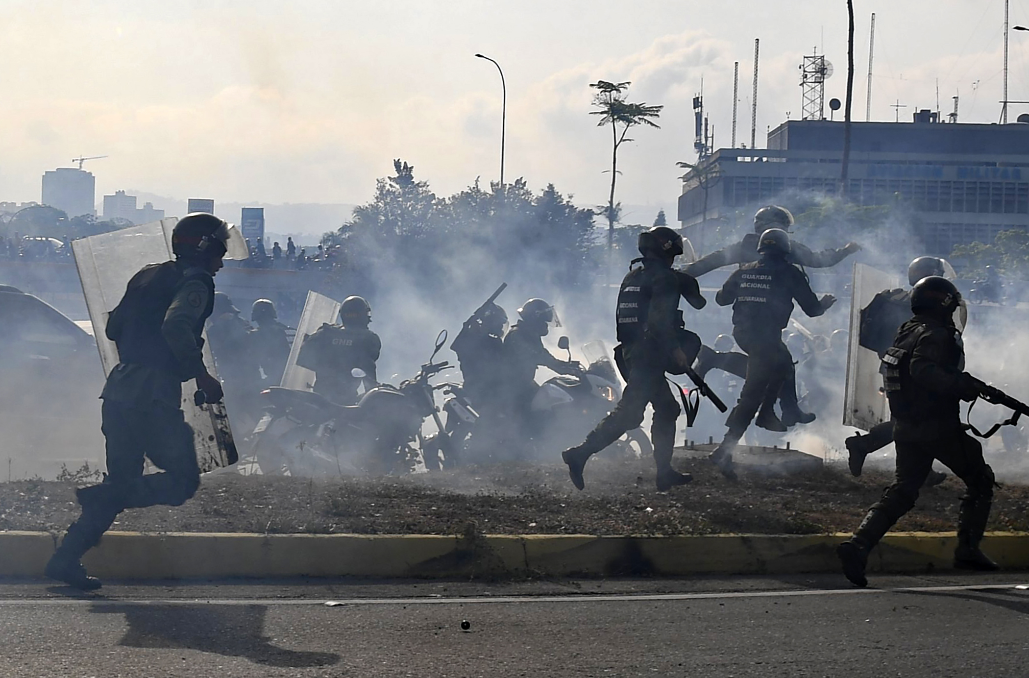 Members of the Bolivarian National Guard loyal to Venezuelan President Nicolas Maduro run under a cloud of tear gas after being repelled with rifle fire by guards supporting Venezuelan opposition leader and self-proclaimed acting president Juan Guaido in front of La Carlota military base in Caracas on April 30, 2019. - Guaido said on Tuesday that troops had joined his campaign to oust President Nicolas Maduro as the government vowed to put down what it called an attempted coup. (Photo by Yuri CORTEZ / AFP) (Photo credit should read YURI CORTEZ/AFP/Getty Images)