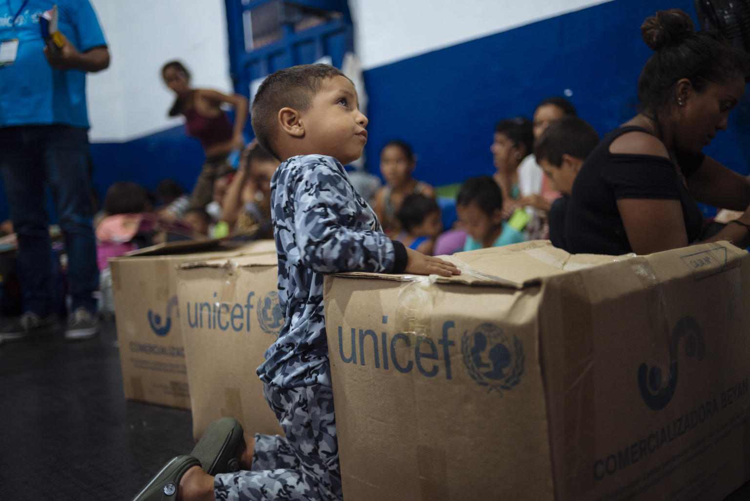 On 24 April 2019 in Cucuta in Colombia, children play near boxes of UNICEF humanitarian supplies at the Samaritan's Purse resting point for walkers who will continue their journey from Venezuela by foot. In February 2019, countries in Latin America and the Caribbean are hosting approximately 2.7 million Venezuelan migrants and refugees of the 3.377.252 million Venezuelans migrating worldwide. Based on inter-agency projections, UNICEF estimates that in 2019, over 1.1 million children will need assistance in Brazil, Colombia, Ecuador, Guyana, Panama, Peru and Trinidad and Tobago. Those in need include Venezuelan migrants and refugees, host communities and non-Venezuelans returnees. During the first two months of 2019, the political and social situation in Colombia underwent significant changes, culminating in closure of the six formal crossing points along the 1,400 km border between the two countries and the militarization of certain informal crossing points and river routes. This blanket closure was subsequently loosened to permit the crossing of urgent medical cases and school children at international bridges. Several thousand school children living in Venezuela have been crossing daily for several years to take classes in Colombian schools in Cucuta. The number of migrants using non-formal crossing sites such as rural paths or trochas and rivers to access certain Colombia sites increased significantly over the reporting period. UNICEF continues to operate its humanitarian activities in the prioritized sites of three main border departments (Arauca, Norte de Santander and La Guajira) as well as in six other departments across the country. Technical support continues to key governmental institutions such as the Colombian Institute for Family Welfare (ICBF), the Ministry of Health (MoH) and the Ministry of Education (MoE) to support capacity building and strengthen the rights of children and adolescents within the overall response. UNICEF has identified seven st