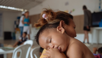 On 25 April 2019 in Colombia, a baby rests on his mother's shoulder at the Friendly Space (CATM) in Cucuta, where UNICEF provides learning activities for migrant children and parents from Venezuela. The programme is supported by UNICEF, in coordination with OIM and the Colombian Chancellery. In February 2019, countries in Latin America and the Caribbean are hosting approximately 2.7 million Venezuelan migrants and refugees of the 3.377.252 million Venezuelans migrating worldwide. Based on inter-agency projections, UNICEF estimates that in 2019, over 1.1 million children will need assistance in Brazil, Colombia, Ecuador, Guyana, Panama, Peru and Trinidad and Tobago. Those in need include Venezuelan migrants and refugees, host communities and non-Venezuelans returnees. During the first two months of 2019, the political and social situation in Colombia underwent significant changes, culminating in closure of the six formal crossing points along the 1,400 km border between the two countries and the militarization of certain informal crossing points and river routes. This blanket closure was subsequently loosened to permit the crossing of urgent medical cases and school children at international bridges. Several thousand school children living in Venezuela have been crossing daily for several years to take classes in Colombian schools in Cucuta. The number of migrants using non-formal crossing sites such as rural paths or trochas and rivers to access certain Colombia sites increased significantly over the reporting period. UNICEF continues to operate its humanitarian activities in the prioritized sites of three main border departments (Arauca, Norte de Santander and La Guajira) as well as in six other departments across the country. Technical support continues to key governmental institutions such as the Colombian Institute for Family Welfare (ICBF), the Ministry of Health (MoH) and the Ministry of Education (MoE) to support capacity building and strengthen the righ