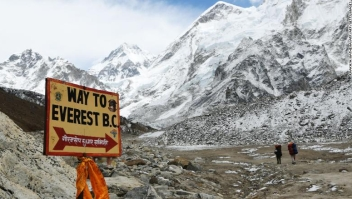 In this photograph taken on April 26, 2018, a sign points towards the Everest base camp while two trekkers walk in the Everest region in Solukhumbu district some 140km northeast of Nepal's capital Kathmandu. - The route is a busy gateway for tourists, climbers and porters heading to the Mount Everest region in Nepal. (Photo by PRAKASH MATHEMA / AFP) (Photo credit should read PRAKASH MATHEMA/AFP/Getty Images)