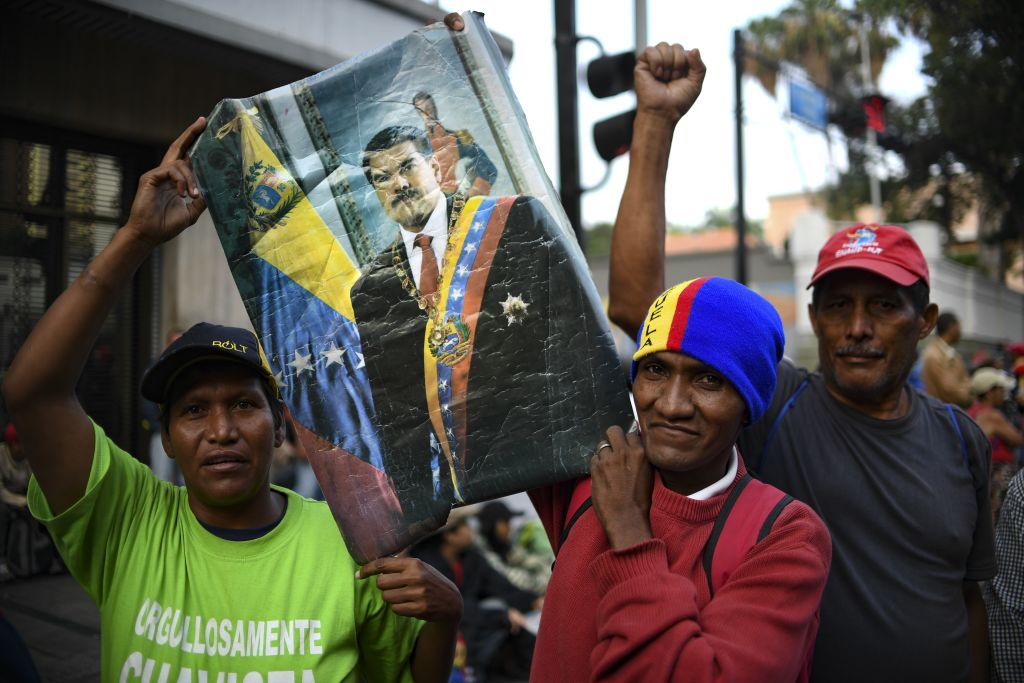 Supporters of the Venezuela's President Nicolas Maduro who stay on vigil in front of the Presidential Palace of Miraflores pose with a poster in Caracas, Venezuela on May 1, 2019. - Demonstrators clashed with police on the streets of the Venezuelan capital Tuesday, spurred by opposition leader Juan Guaido's call on the military to rise up against President Nicolas Maduro -- who said he had defeated an attempted coup. (Photo by YURI CORTEZ / AFP) (Photo credit should read YURI CORTEZ/AFP/Getty Images)