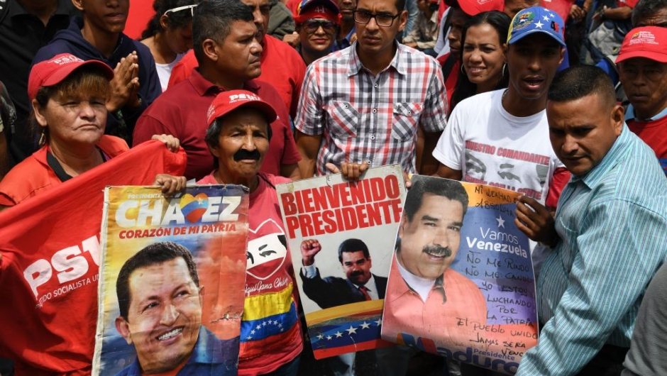Supporters of Venezuelan President Nicolas Maduro display placard with pictures of Maduro and late leader Hugo Chavez during a rally on May Day in Caracas on May 1, 2019. - Pro- and anti-government rallies were due to take place in Venezuela, a day after violent clashes erupted in the capital following opposition leader Juan Guido's call on the military to rise up against Maduro, who claimed the insurrection had failed. (Photo by Yuri CORTEZ / AFP) (Photo credit should read YURI CORTEZ/AFP/Getty Images)