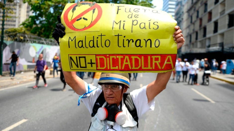 An opposition demonstrator holds a placard against Venezuelan President Nicolas Maduro as he takes part in a demonstration in Caracas to commemorate May Day on May 1, 2019 after a day of violent clashes on the streets of the capital spurred by opposition leader Juan Guaido's call on the military to rise up against Maduro. - Guaido called for a massive May Day protest to increase the pressure on President Maduro. (Photo by Matias DELACROIX / AFP) (Photo credit should read MATIAS DELACROIX/AFP/Getty Images)