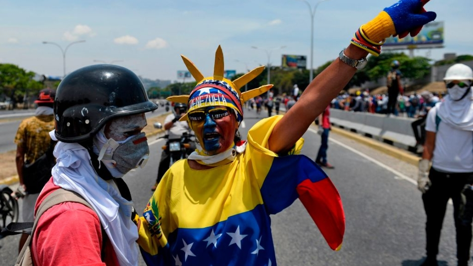 Anti-government protesters take part in a march in Caracas to commemorate May Day on May 1, 2019 after a day of violent clashes on the streets of the capital spurred by Venezuela's opposition leader Juan Guaido's call on the military to rise up against President Nicolas Maduro. - Guaido called for a massive May Day protest to increase the pressure on President Maduro. (Photo by Matias Delacroix / AFP) (Photo credit should read MATIAS DELACROIX/AFP/Getty Images)