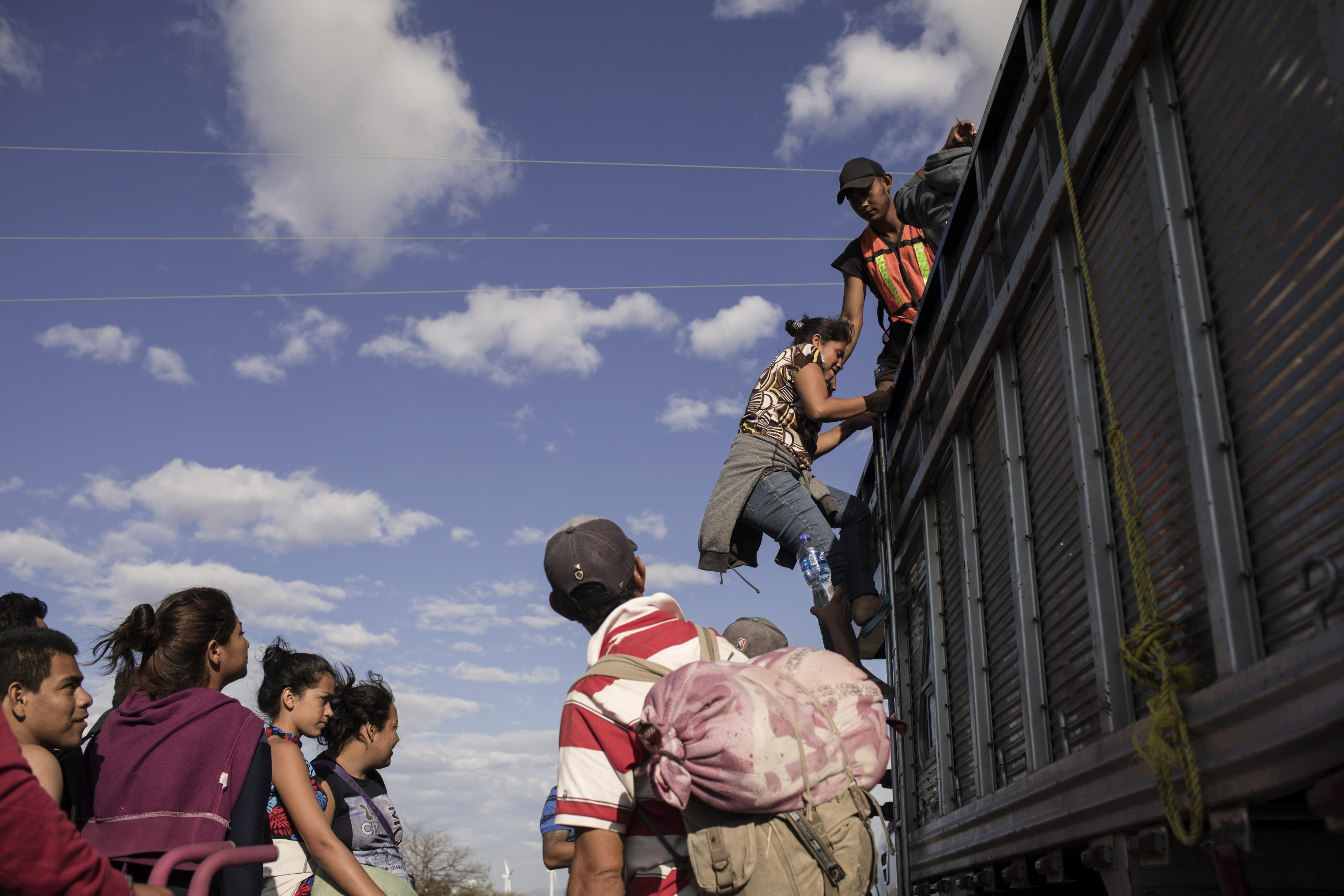 A group of Central American refugees and asylum seekers, led by the non-profit humanitarian organization Pueblos Sin Fronteras (People Without Borders), board a truck offering a ride to their next destination in the town of Santiago Niltepec, Oaxaca state, Mexico, on Saturday, March 31, 2018. The Trump administration is crafting legislation to make it harder for refugees to gain asylum in the U.S. and loosen restrictions on detaining immigrants apprehended near the border, a senior White House official said. Photographer: Jordi Ruiz Cirera/Bloomberg